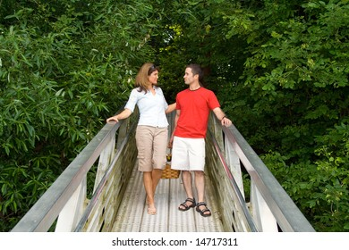 A couple, standing together, smiling and staring at each other on a dock ramp, near the exit. - horizontally framed