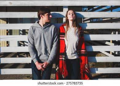 A couple standing at the wooden wall