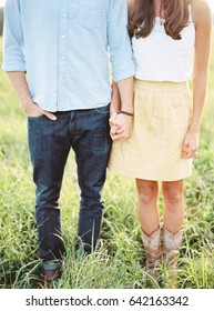 Couple Stands in Field Holding Hands
