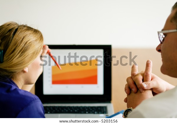 A couple starting up a business discussing market trends (shallow depth of field, focus on face of the girl)