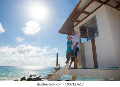 Couple staying at the porch of tiny house or beach watchers house at the caribbean seashore. Man is leaning on the wall of house, and his wife or girlfriend leaning on him. The Turquoise water behind.