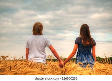 Couple staying at a wheat field at sunset time
