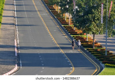 Couple step on pedestrian walking lane in the road around stadium, slow and relaxing exercise, beautiful architecture landscape.