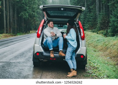 couple stop to drink hot tea. road trip concept. sitting in suv trunk at road side in mountains forest. lifestyles