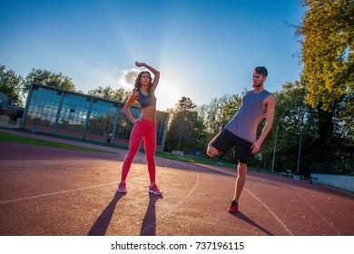 Couple stretching on the stadium