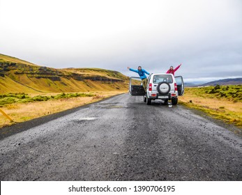 A couple stretching from the sides of the car and waving at the camera. The car is pulled on the side of the road, next to mountains. Mountains are overgrown with yellow and green grass. Fun moments