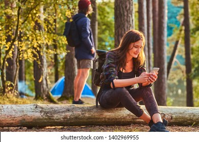 Couple of students are chilling in the forest. Man is standing near tent. Girl is sitting on a log while chatting on a a smartphone.