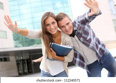 Couple of students having fun in front of university building