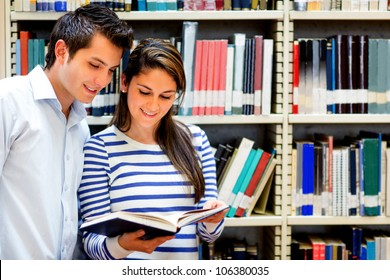 Couple of students at the library reading a book