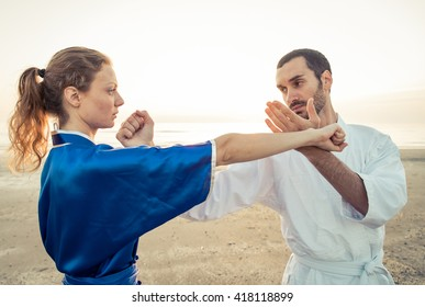 Couple of students training martial arts on the beach. parry and hit in kung fu style