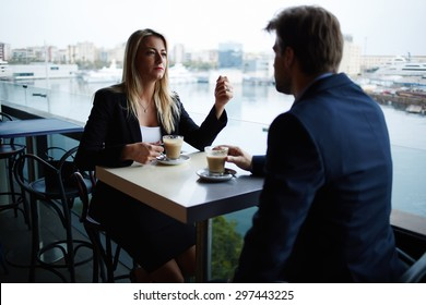 Couple of successful influential leaders having meeting discussion while they drinking cafe, business people talking to each other during coffee break in modern luxury place with sea marina port view
