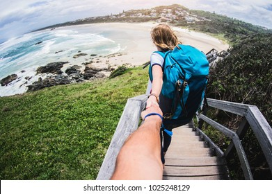 Couple summer vacation travel. Woman walking holding hand of husband following her, view from behind