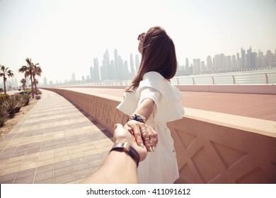 Couple summer vacation travel. Woman walking on romantic honeymoon promenade holidays holding hand of husband following her, view from behind. (focus on woman)