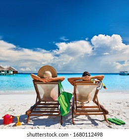Couple in sun beds on a tropical beach at Maldives