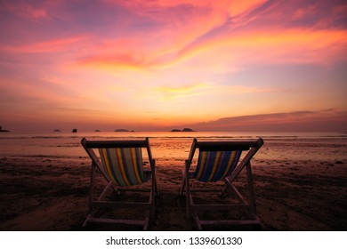 Couple of sun loungers on the beach during amazing sunset.