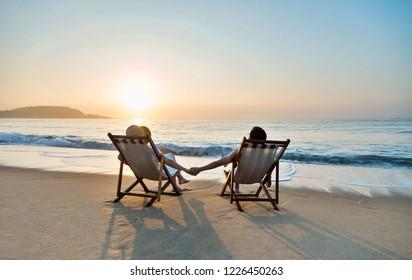 Couple sunbathing on a beach chair.