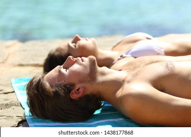 Couple sunbathing on summer vacation on the beach with the man in foreground
