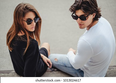 Couple with sunglasses posing outside with attitude for the camera