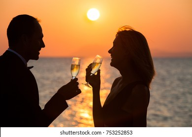 couple at sunset on the beach with glasses of champagne