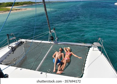 Couple suntanning on a catamaran net