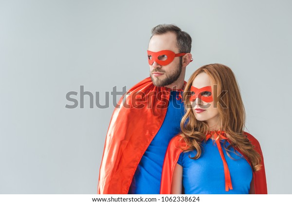 couple in superhero costumes standing together and looking away isolated on grey