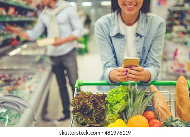 Couple in the supermarket. Cropped image of girl leaning on shopping cart, using a mobile phone and smiling, in the background her boyfriend is choosing food