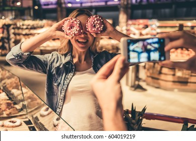 Couple at the supermarket. Girl is holding donuts and posing while her boyfriend is taking a photo