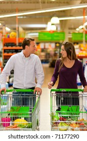 Couple in a supermarket shopping equipped with shopping carts buying groceries; they almost finished