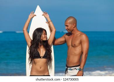 couple with surfboard on beach