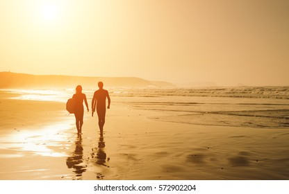 Couple of surfers leaving the water after surfing on a beautiful sunset at the beach. Body board and surf lifestyle concept.