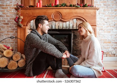 Couple in sweaters sitting on the floor near the fireplace. eyes to eyes