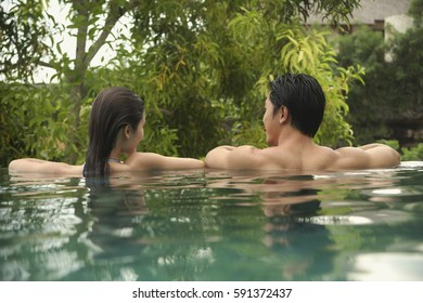 Couple in swimming pool, rearview