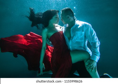 Couple swimming underwater with beautiful dress - Artistic dreamy portrait