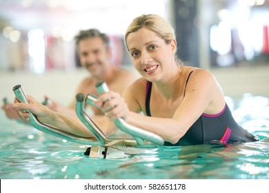 Couple in swimming-pool doing aquabike exercises
