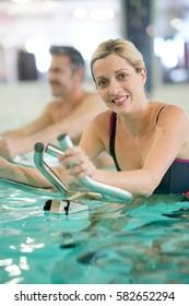 Couple in swimming-pool doing aquabike exercises