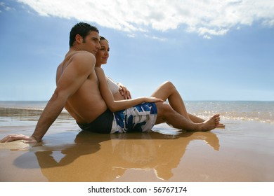 Couple in swimsuit laid on the sand face to the sea