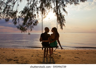 Couple swinging on a swing against a background of sea sunset