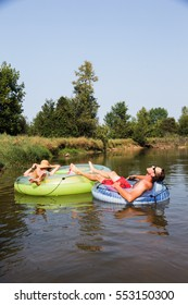 A couple take float in tubes down the river during the summer.