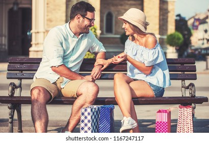 Couple take a rest after shopping and enjoying in conversation in the city park. Consumerism, love, dating, lifestyle concept
