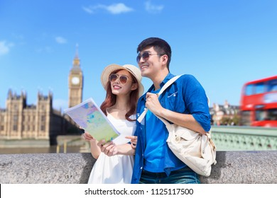 couple take world map and travel to london