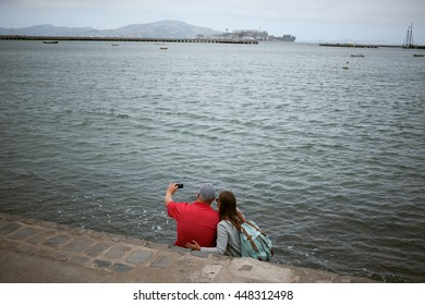 A couple takes a selfie near water on an overcast day