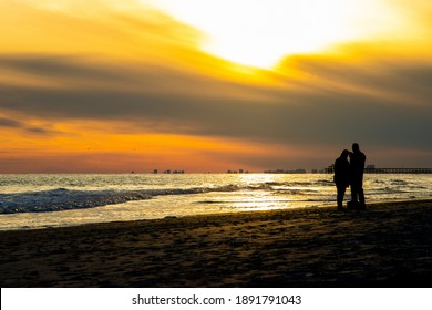 A couple takes a selfie with a phone on the beach near sunset in a coastal travel destination. The ocean reflects the orange and gold light, turning them into a silhouette.