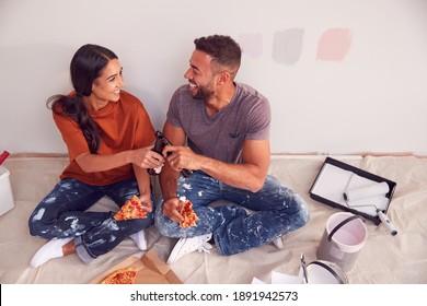 Pareja Tomando Un Descanso Y Bebiendo Cerveza Y Comiendo Pizza Mientras Decoran Su Habitación En Una Nueva Casa Juntos