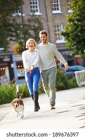 Couple Taking Dog For Walk In City Park