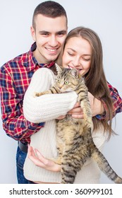 Couple Taking Playing With Pet Cat At Home.happy young couple on the bed at home with their cat