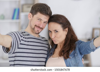 couple taking self portrait indoors