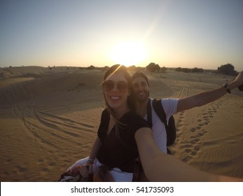 Couple taking a selfie in a camel riding in desert - with Gopro Camera