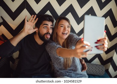 Couple taking a selfie with funny faces.