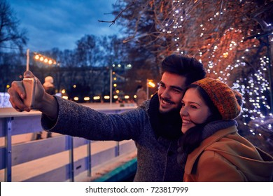 Couple Taking Selfie Near Ice Rink