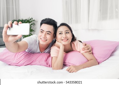 Couple taking selfie with phone lying on bed.